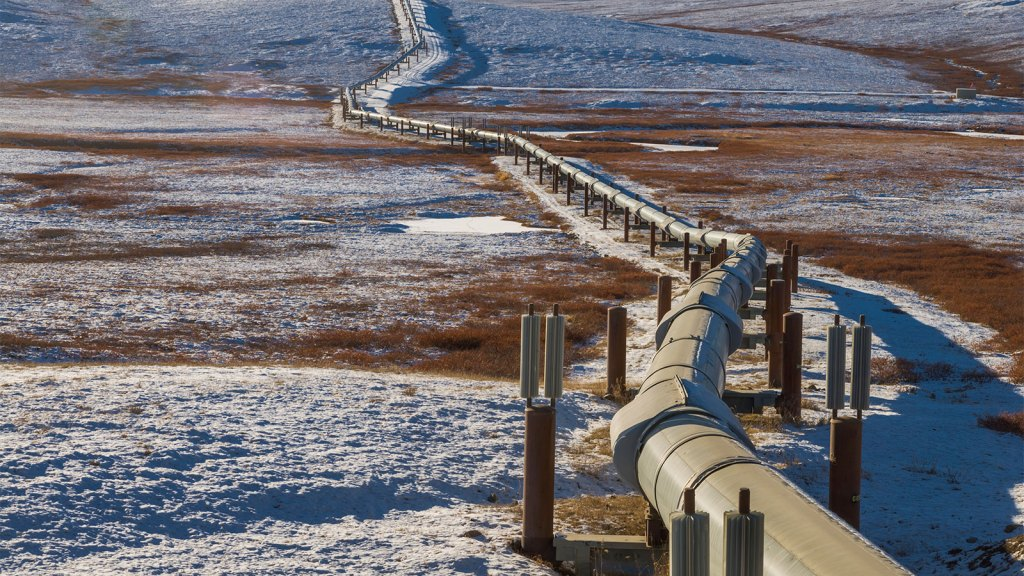A pipeline stretches through partly frozen tundra in Alaska.