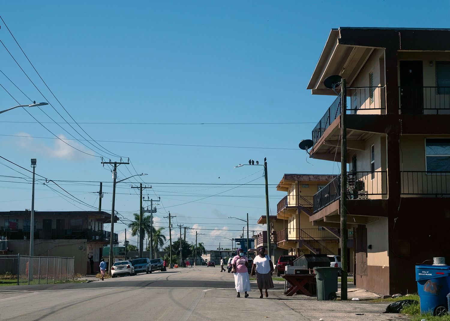 Belle Glade residents wearing masks walk down a street off of Martin Luther King, Jr. Boulevard, as COVID infection rates in Florida reach record highs (left).