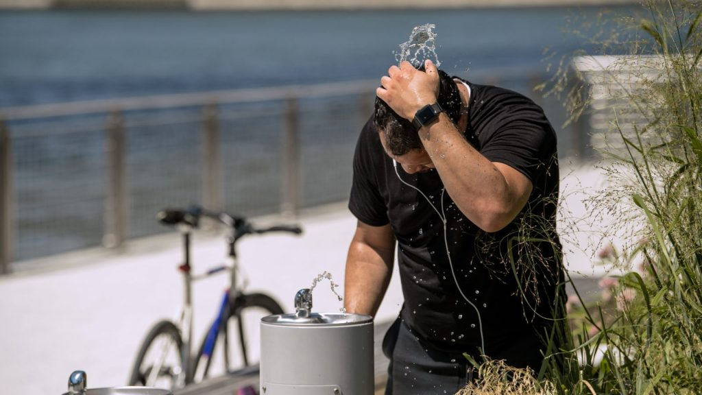A man stands over a water fountain as a heatwave strikes the northeast of the United States.
