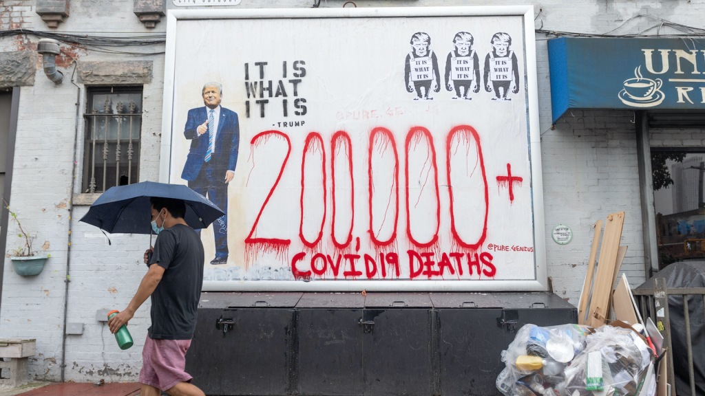 """A man walks by graffiti of Trump and lettering reading """"200,000 COVID-19 deaths."""""""