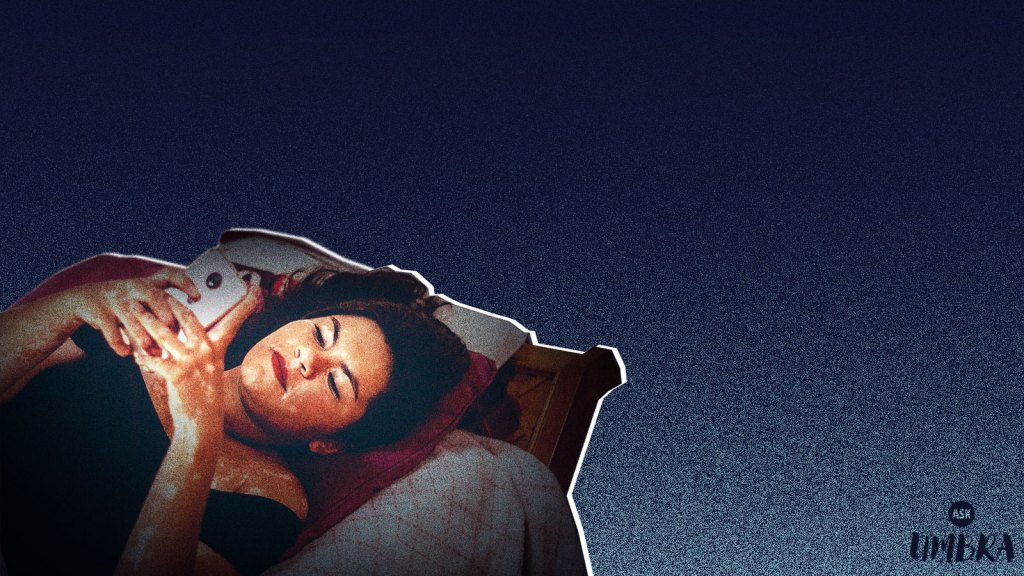 Woman laying in bed looking at phone