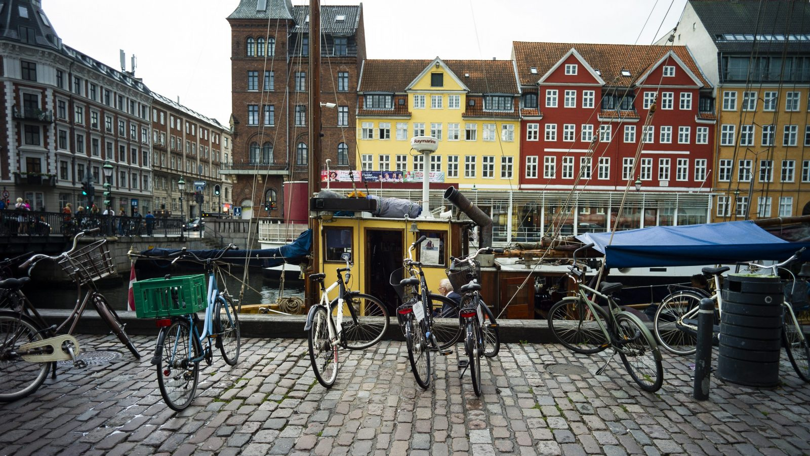 A photo shows a row of bicycles in front of a canal and colorful buildings.