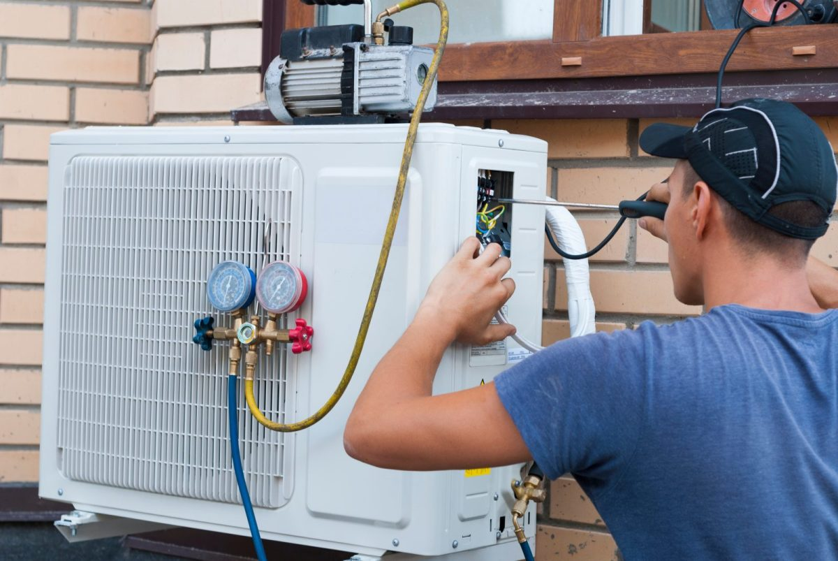A worker turns a screwdriver to hook hoses to a heatpump