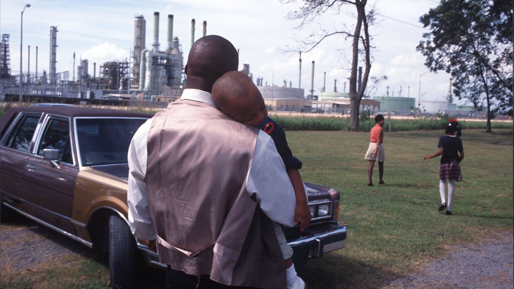 A family leaves Sunday church services surrounded by chemical plants in October of 1998 in Lions, Louisiana.