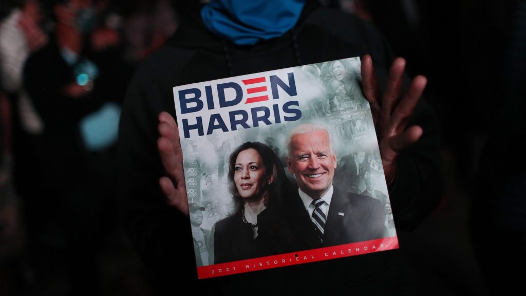 Hands hold calendar showing President-elect Joe Biden And Vice President-elect Kamala Harris