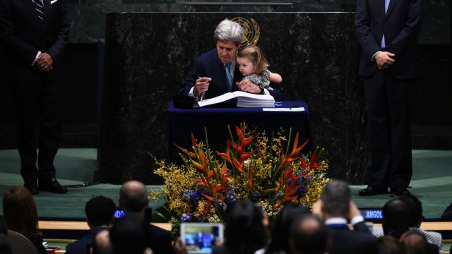 US Secretary of State John Kerry holds his granddaughter, Isabelle Dobbs-Higginson, during the signature ceremony for the Paris Agreement at the United Nations General Assembly Hall in April 2016.