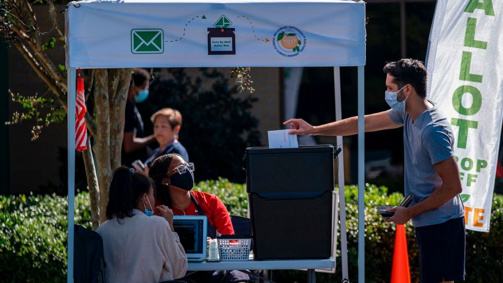A man dropping off his ballot at an Orange County, Florida voting booth