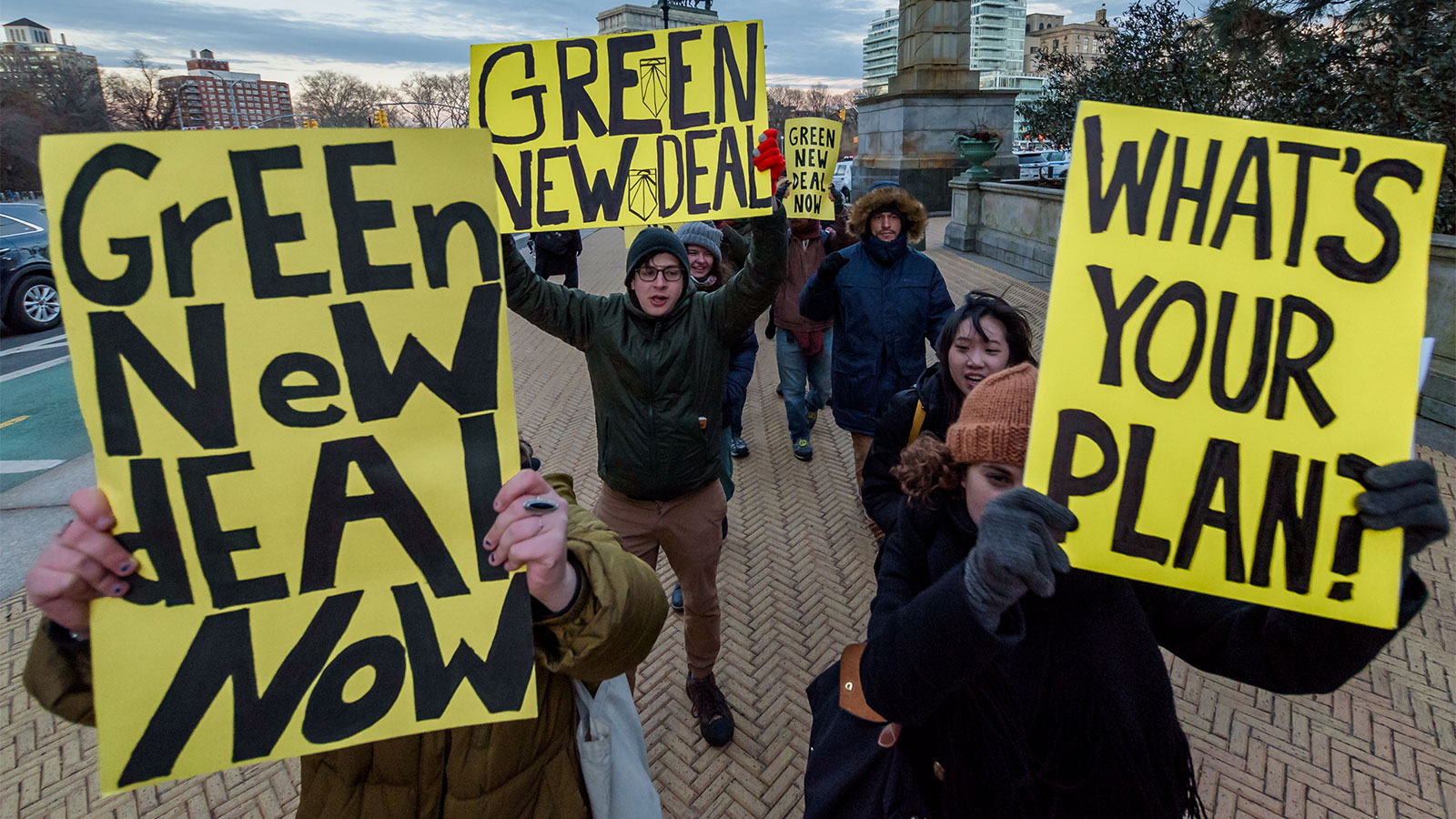 Green New Deal supporters hold signs encouraging action on climate change.
