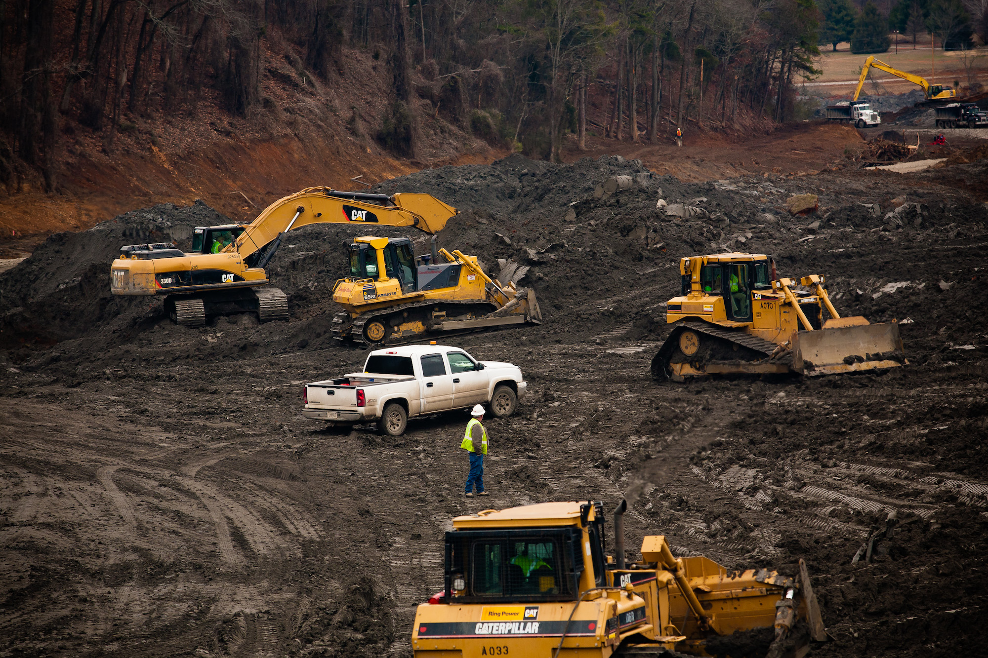A photo of yellow bulldozers and workers in coal ash slurry