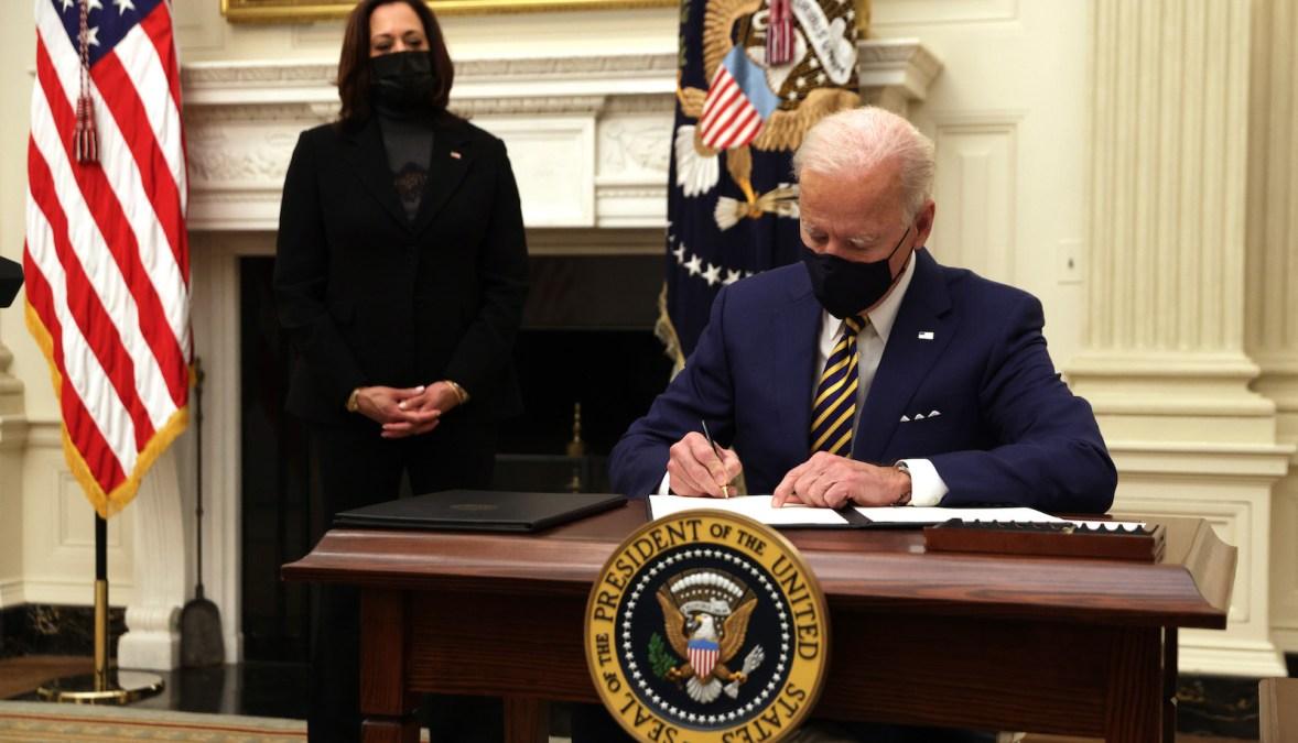 بایدن پشت میز خود دستورهای اجرایی را امضا می کند.