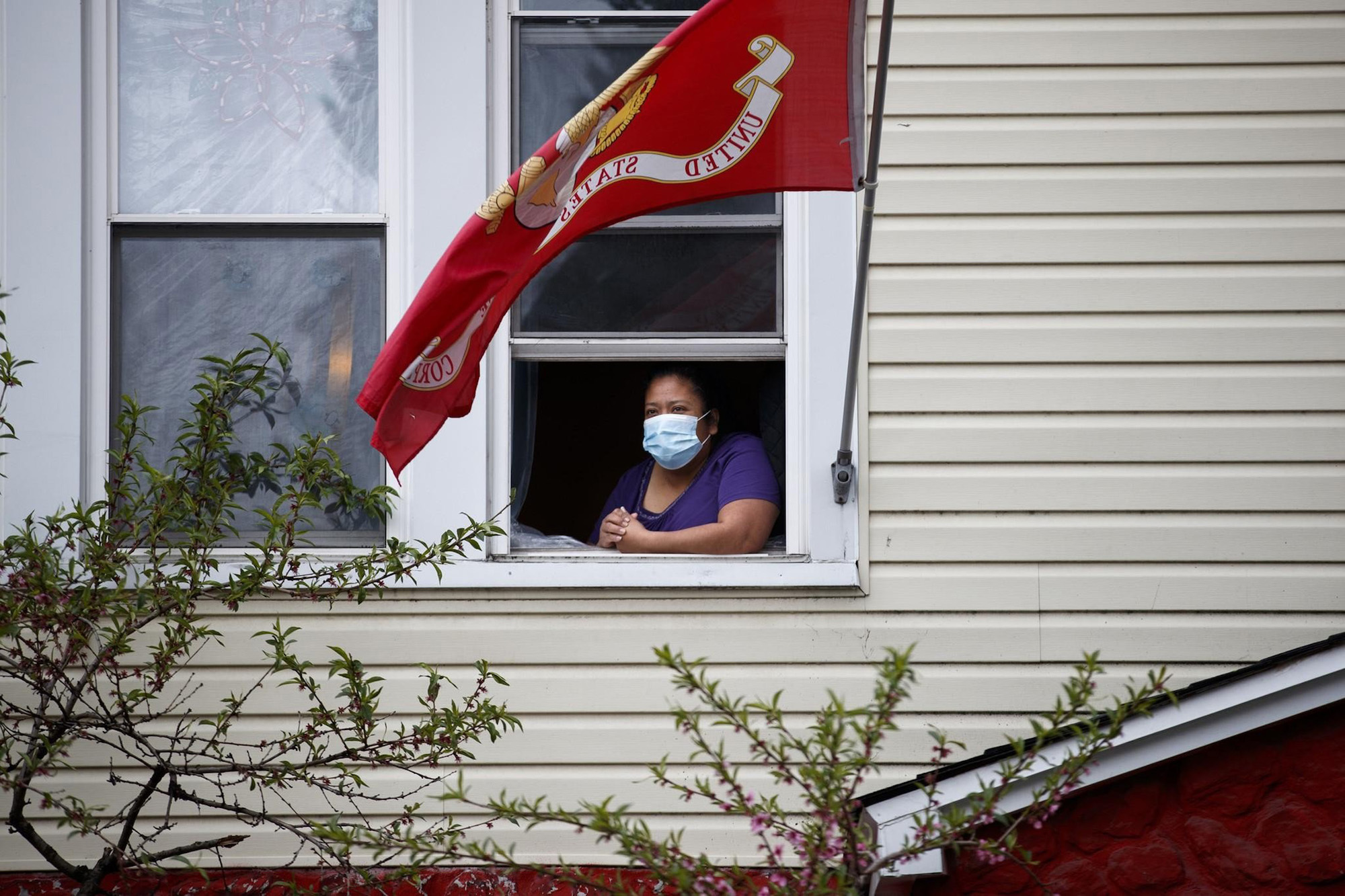 a photo of a woman wearing a surgical mask looking out the window of her home
