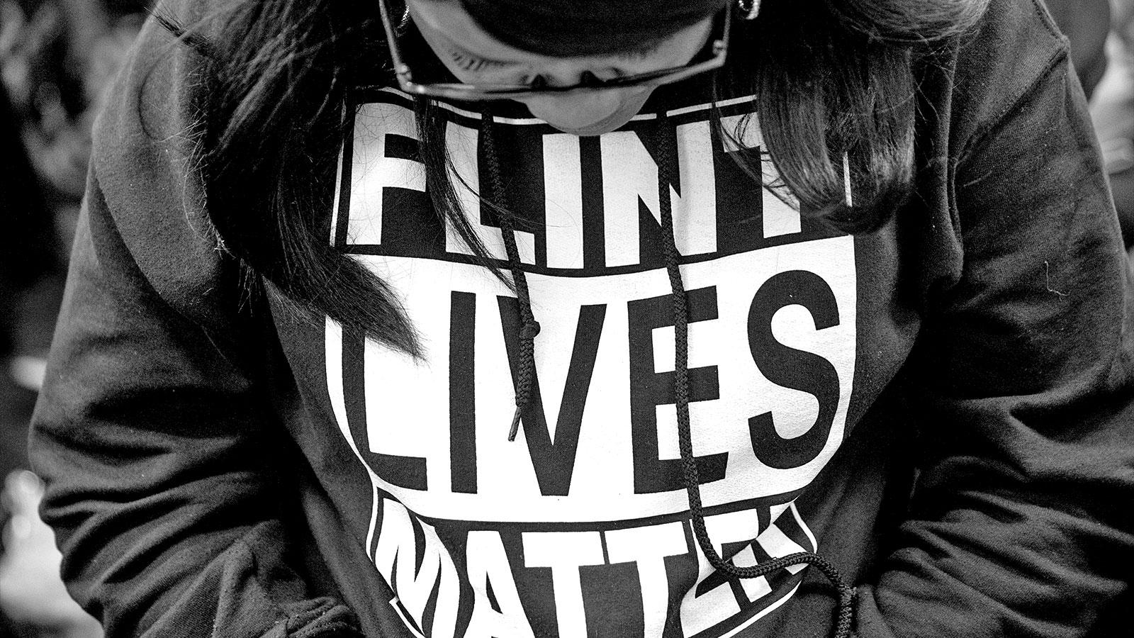 """A close up photograph of a woman wearing a sweatshirt reading """"Flint Lives Matter"""""""