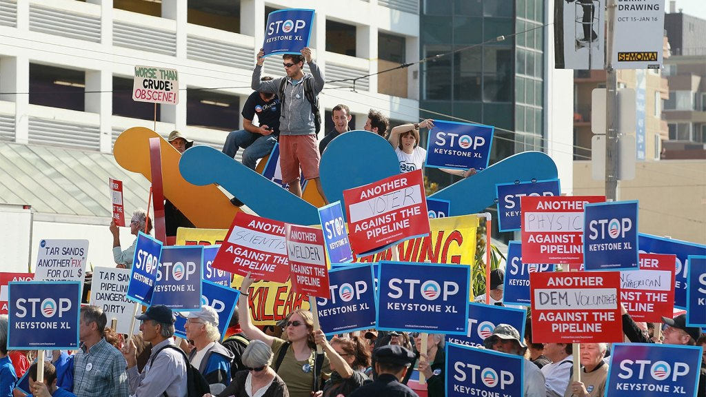 Protestors against the construction of the Keystone XL oil pipeline hold signs and stand on a Keith Haring sculpture as they demonstrate outside of the W Hotel before the arrival of U.S. President Barack Obama on October 25, 2011 in San Francisco, California