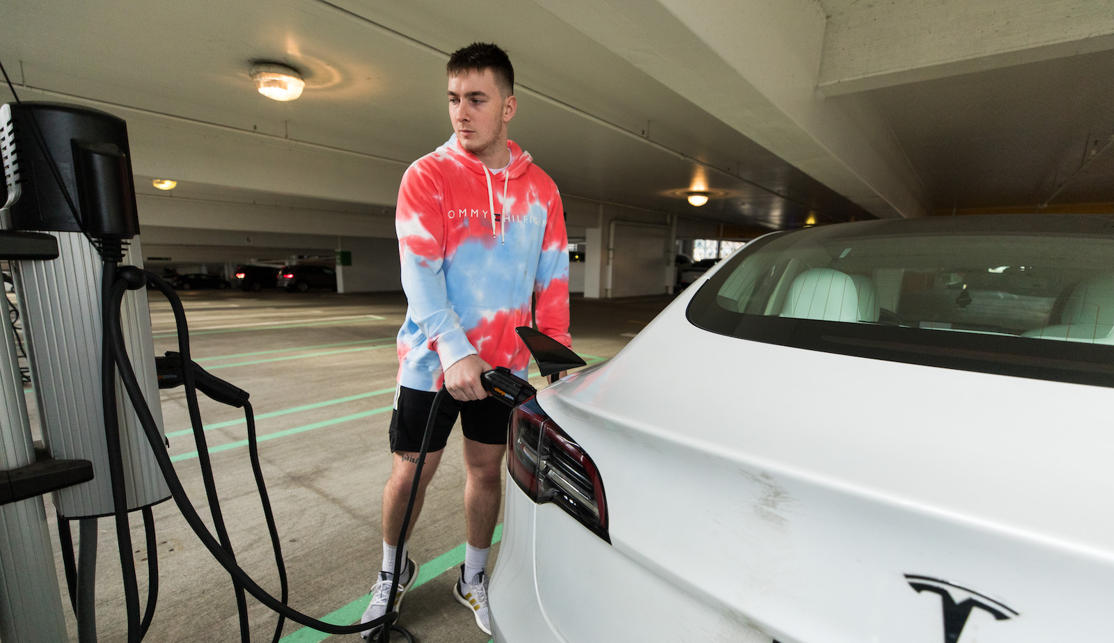 driver charging an electric car