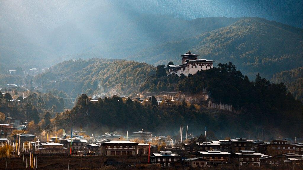 Uma fotografia da cidade de Jakar e Dzong no Butão, com raios de sol rompendo a névoa da manhã.