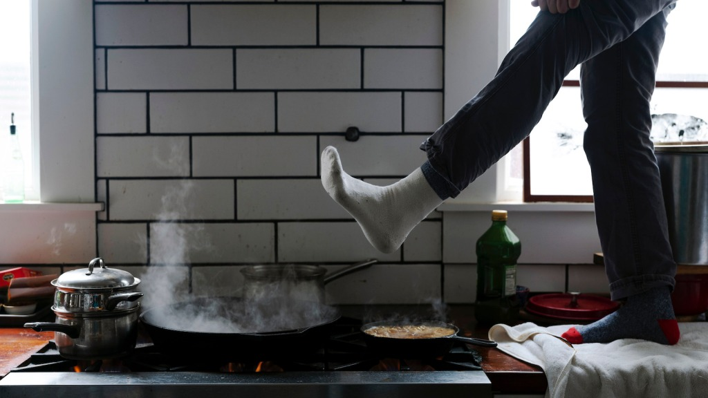 A person stands on a kitchen counter with their foot extended over their gas stove for warmth