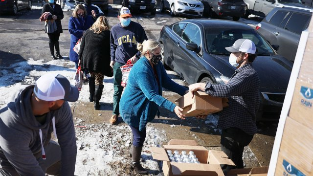 Mark Majkrzak gives out bottles of Rain Pure Mountain Spring Water to people in need on February 19, 2021 in Austin, Texas.