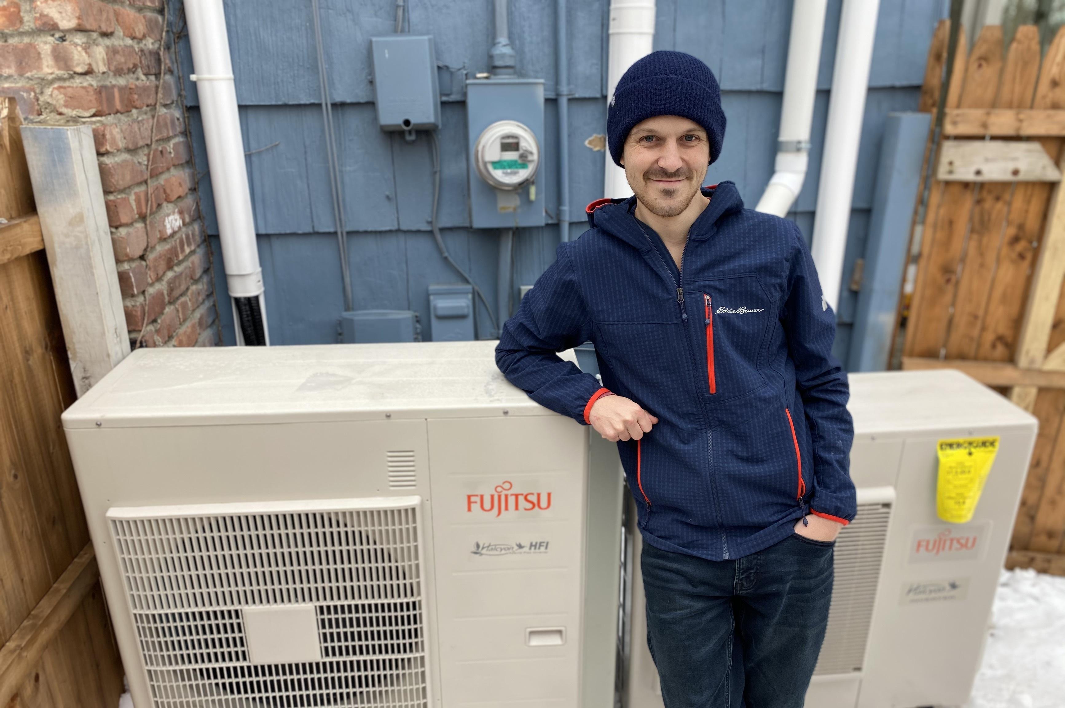 Adam James standing next to the outdoor unit of his new heat pump