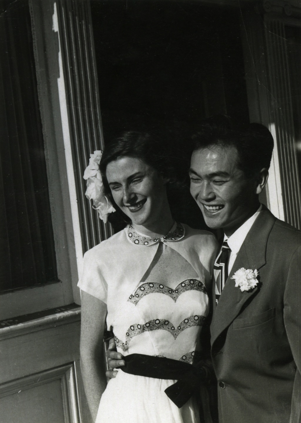 A black and white photo of Dorothy Walker and Joe Kamiya with their arms around each other and smiling in front of a house