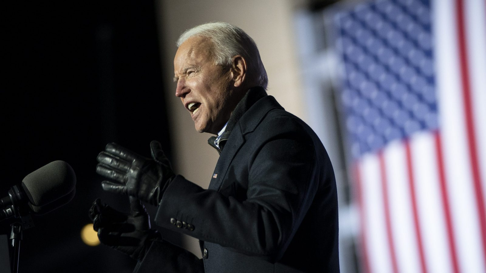 A photo of Joe Biden at a podium speaking. He is wearing a dark coat and dark gloves.
