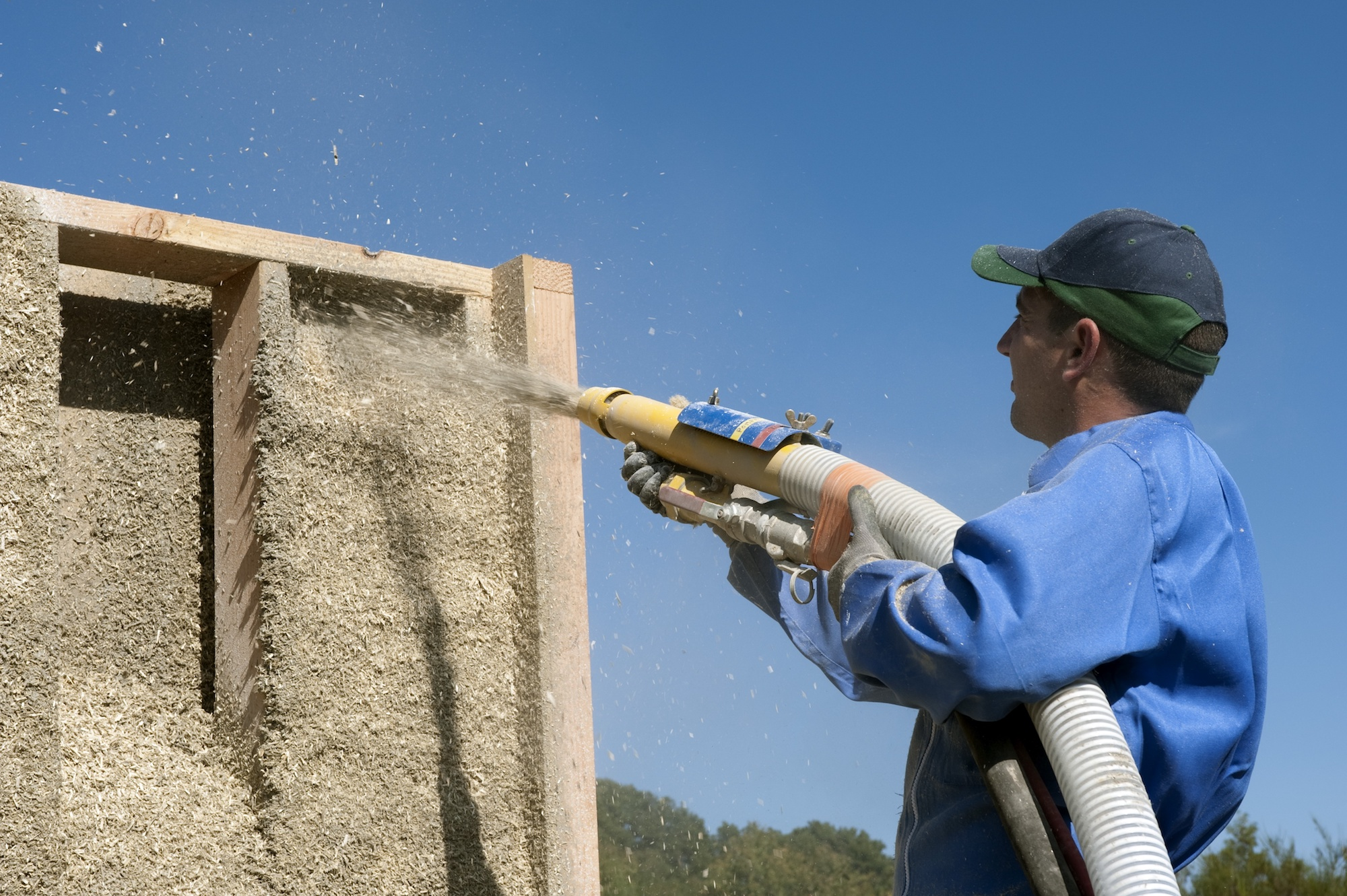 A man in a blue shirt and baseball cap holds a spray hose blasting out a mixture of small bits of hemp into a wooden building frame