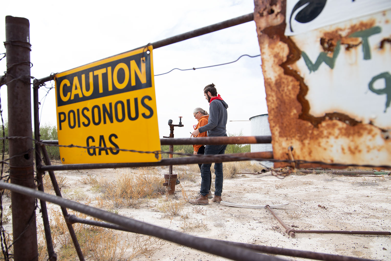 """Two people stand behind a fence with a sign that says """"Caution Poisonous Gas""""."""