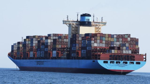 A photo of the container ship Gjertrud Maersk, anchored off the coast of Virginia Beach on June 29, 2020. The large, blue vessel is topped with hundreds of colorful shipping containers