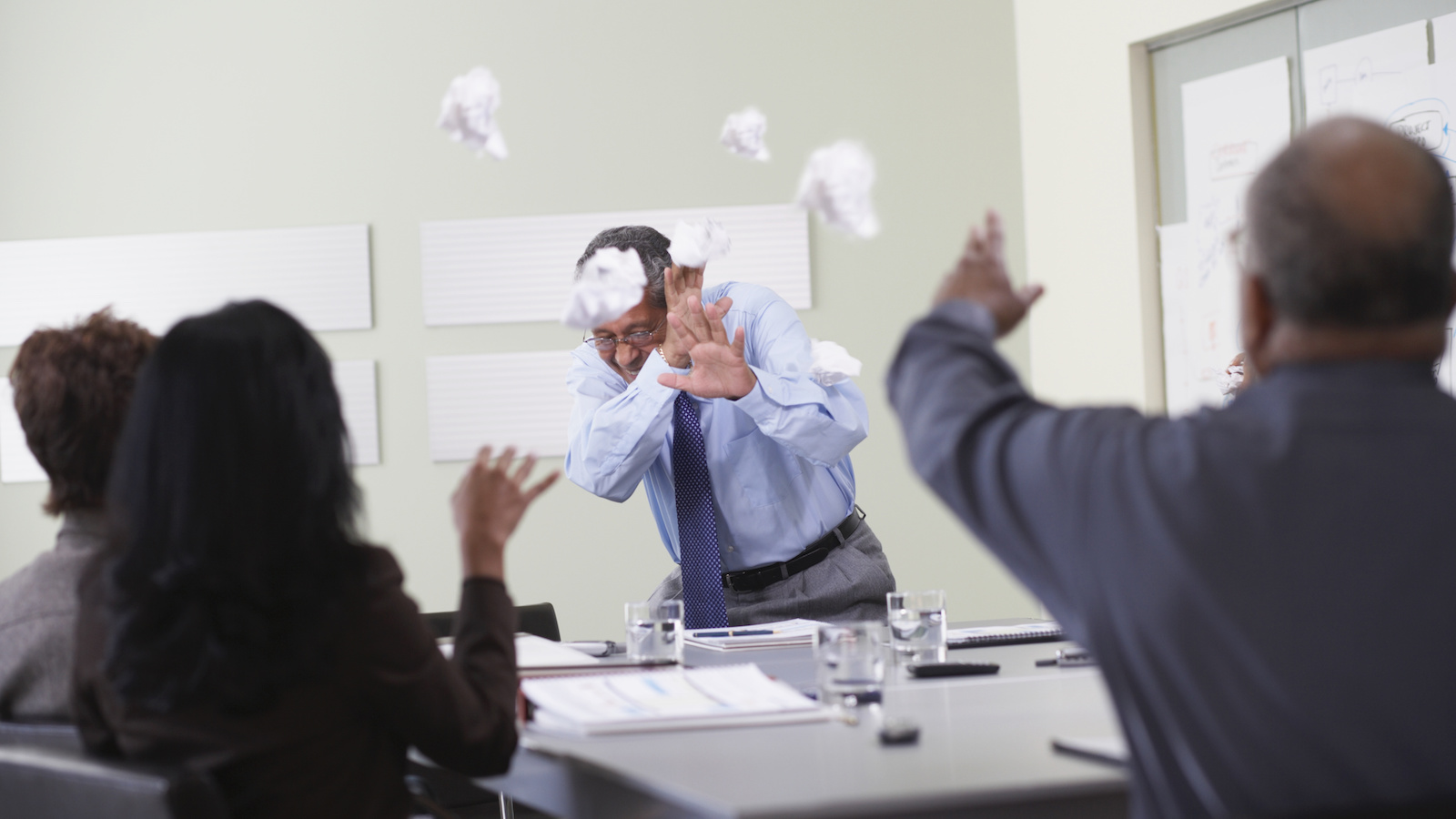 Businessmen throwing paper balls at someone giving a presentation