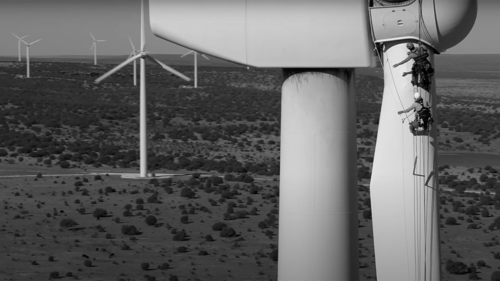 A screenshot from a video targeting builders for climate projects. Shows a landscape with wind turbines up close and in the distance