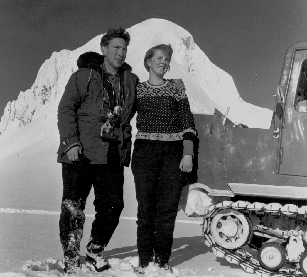A black-and-white photo of a bundled-up couple standing in front of a glacier.