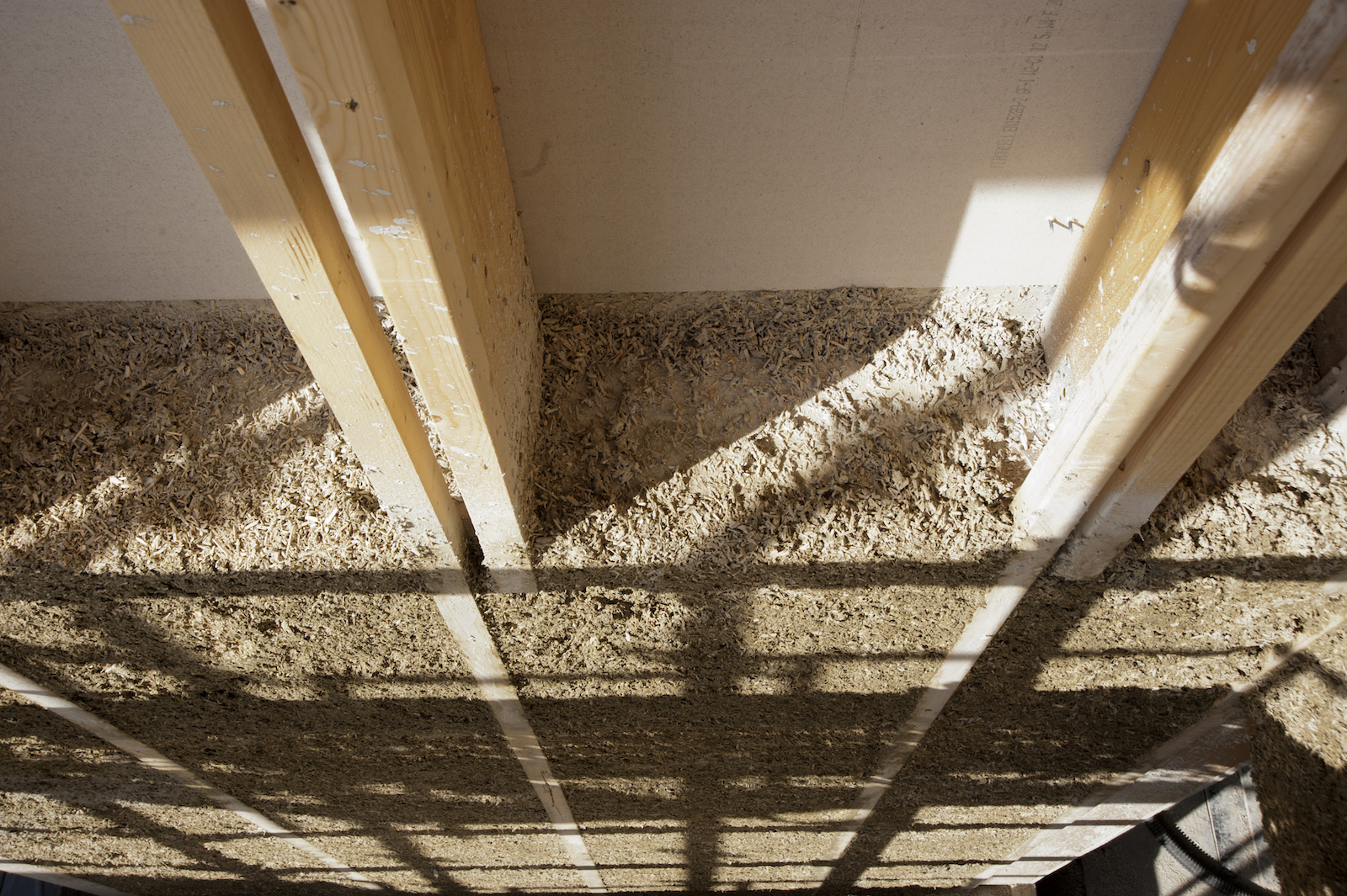 "a photo of a top-down view of the inside of a wall. Long wooden beams run in parallel. In between, grayish rectangles of ""hempcrete"" fill in the gaps. It is porous-looking like a sponge."