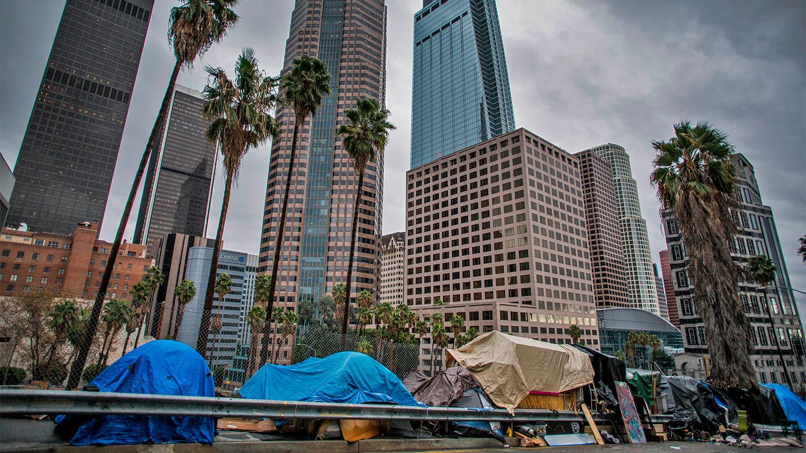 مجموعه ای از چادرها برای افراد بی خانمان در مقابل یک ساختمان بلند در مرکز شهر لس آنجلس.