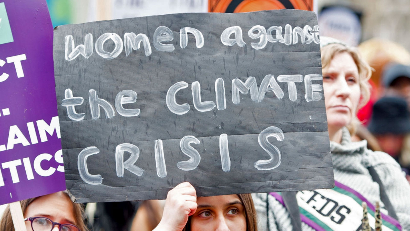 A woman holding a sign that says