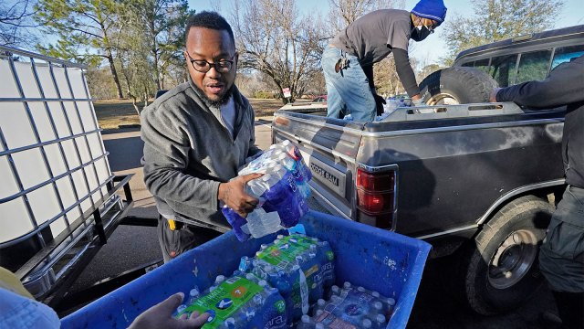 Madonna Manor maintenance supervisor Lamar Jackson left, stacks bottled water brought by Mac Epps of Mississippi Move, as part of the supply efforts by city councilman and State Rep. De'Keither Stamps to a senior residence in west Jackson, Miss.