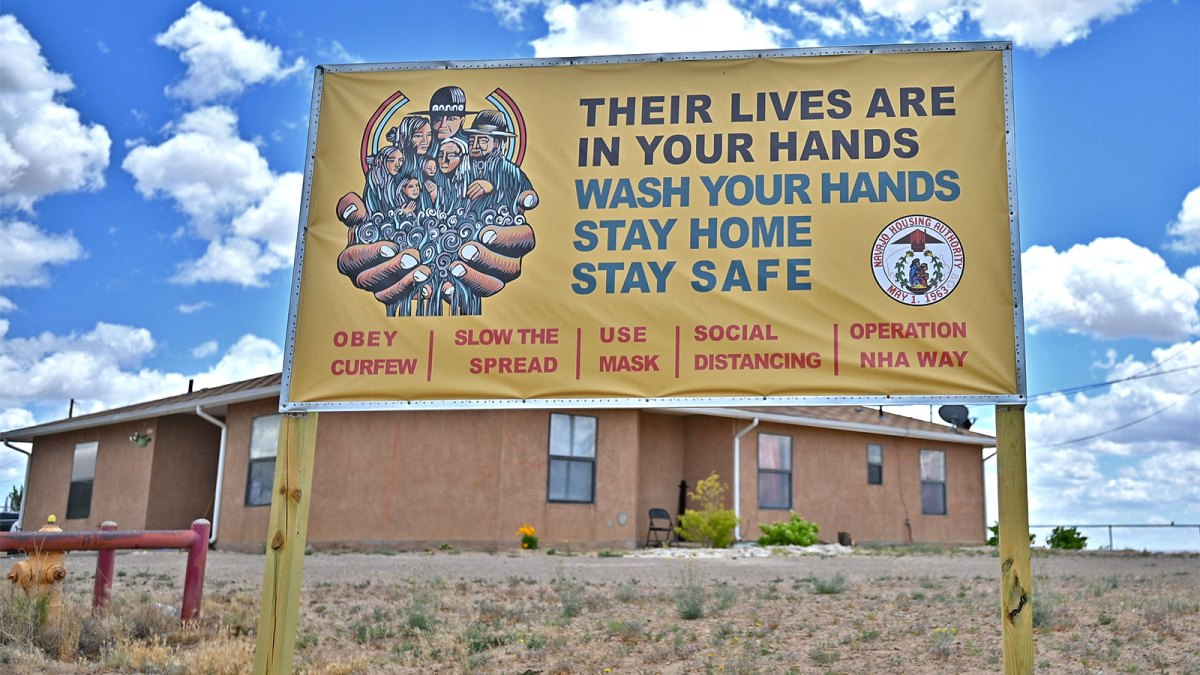A sign displays a message about staying safe from the coronavirus at an entrance to a Navajo Nation housing community.