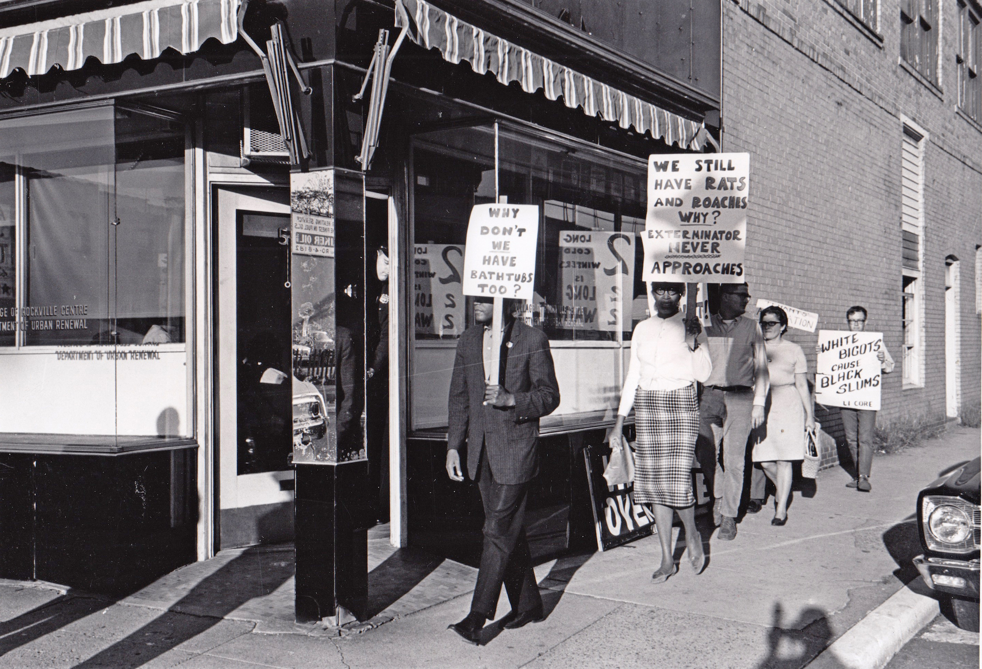 A black and white photo of a group of men and women holding picket signs outside an office