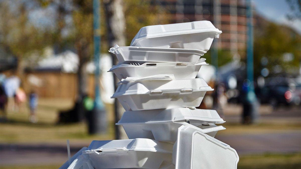 انبوهی از ظروف فوم که روی سطل آشغال انباشته شده است