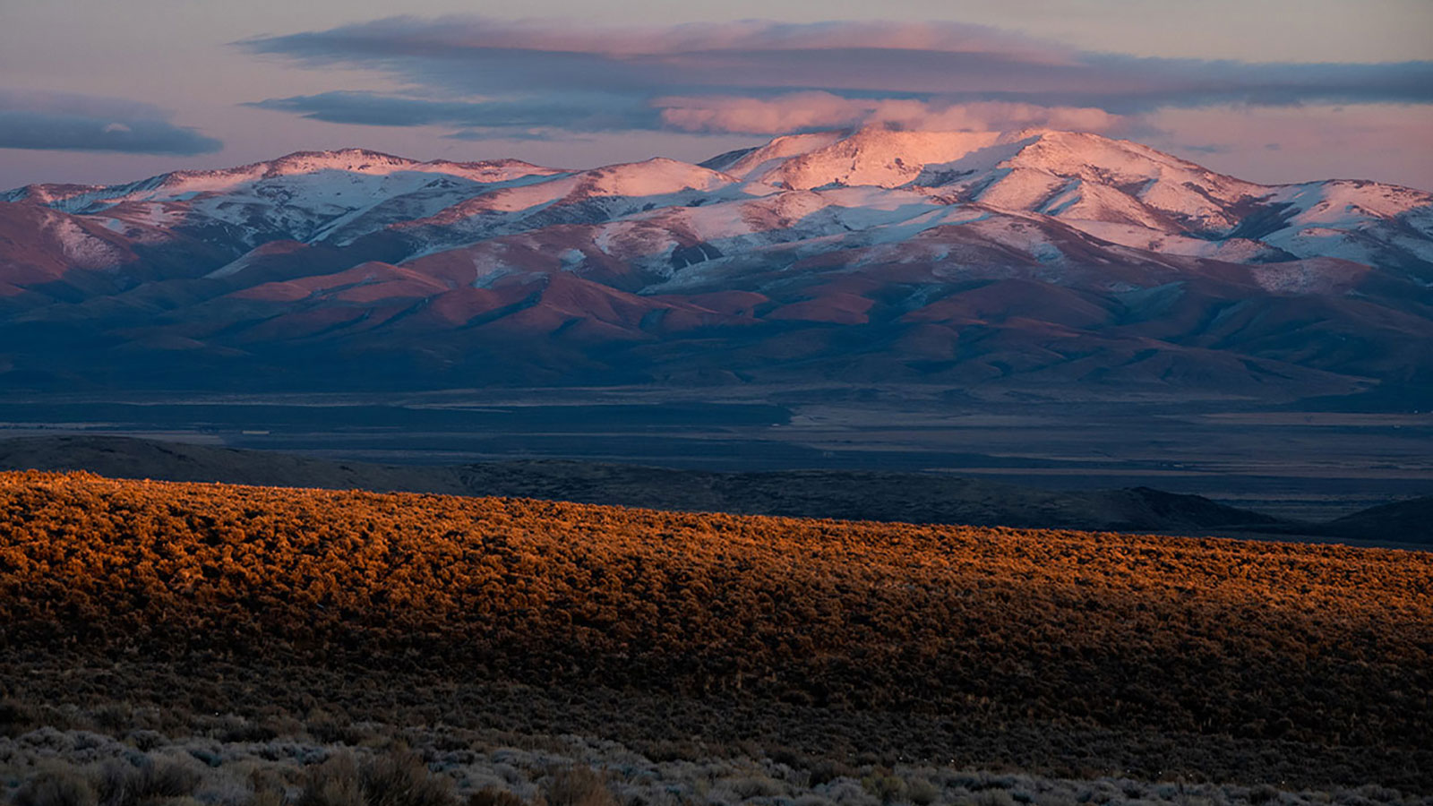Thacker pass at sunset with snow-covered mountains in the background