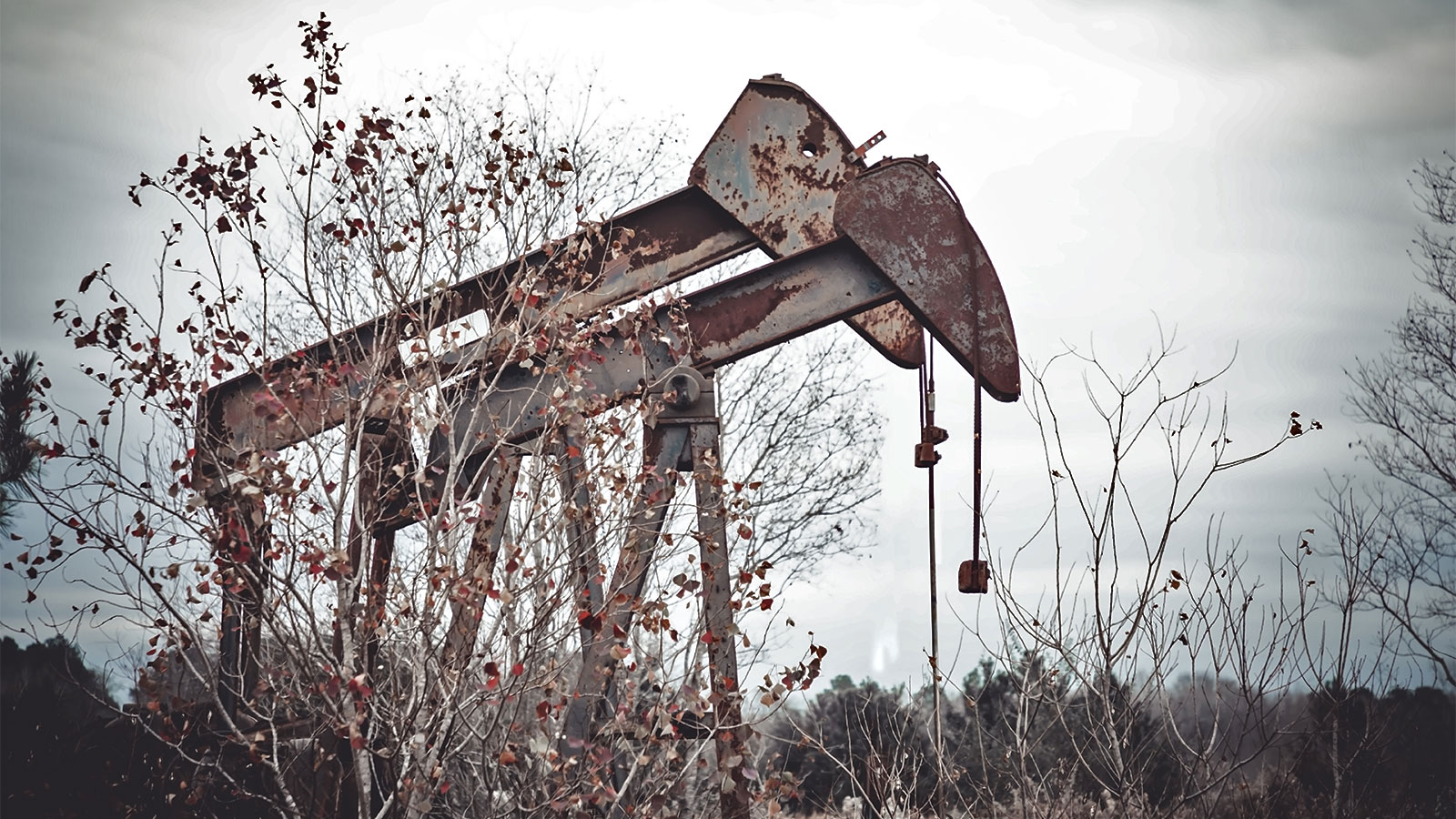 A photograph of rusty abandoned oil pumps in rural Texas.