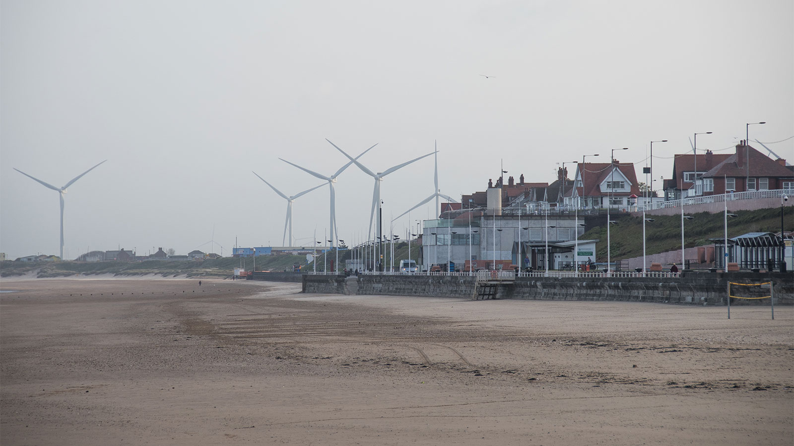 Photo of a beach community with wind turbines in the background