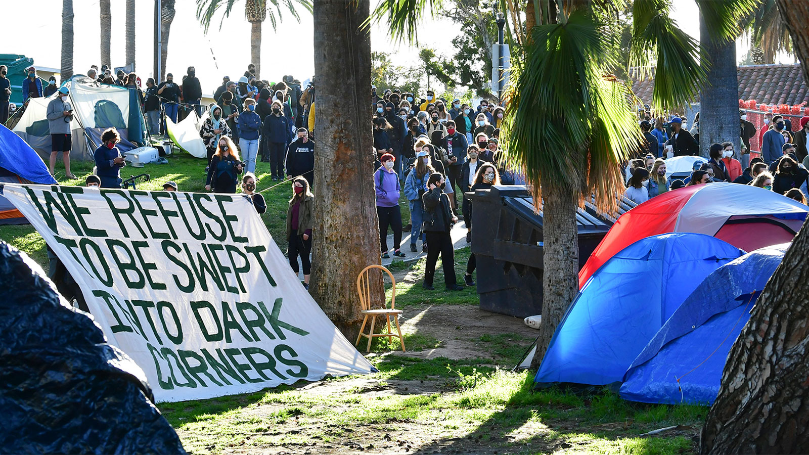 Social activists, homeless residents, and supporters rally at the start of a 24-hour vigil to block a planned shutdown of a homeless encampment at Echo Lake Park in Los Angeles