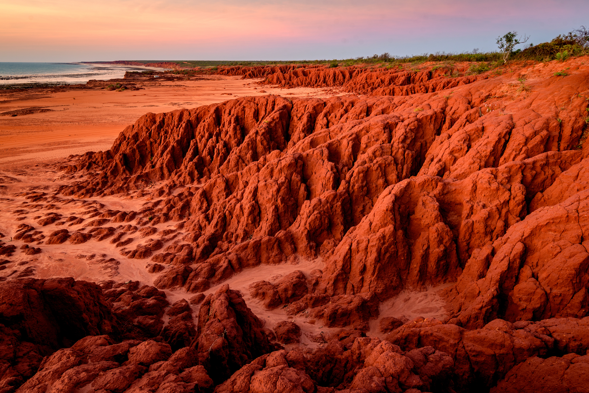 deep red, rocky cliffs stretch from the right side of the screen, melting into sandy beach and blue water