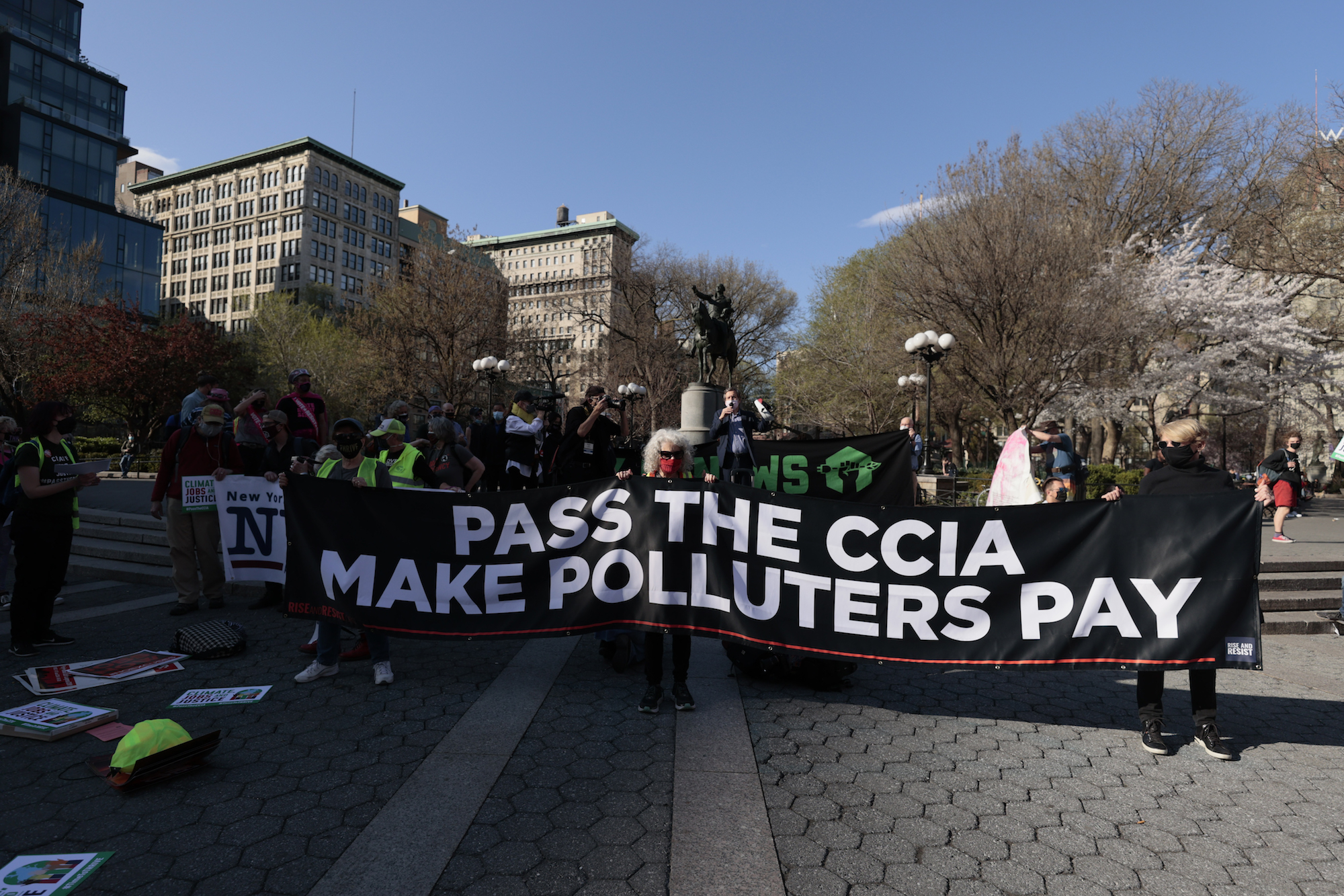 """a group of activists carry a large banner with white letters reading """"PASS THE CCIA MAKE POLLUTERS PAY"""""""