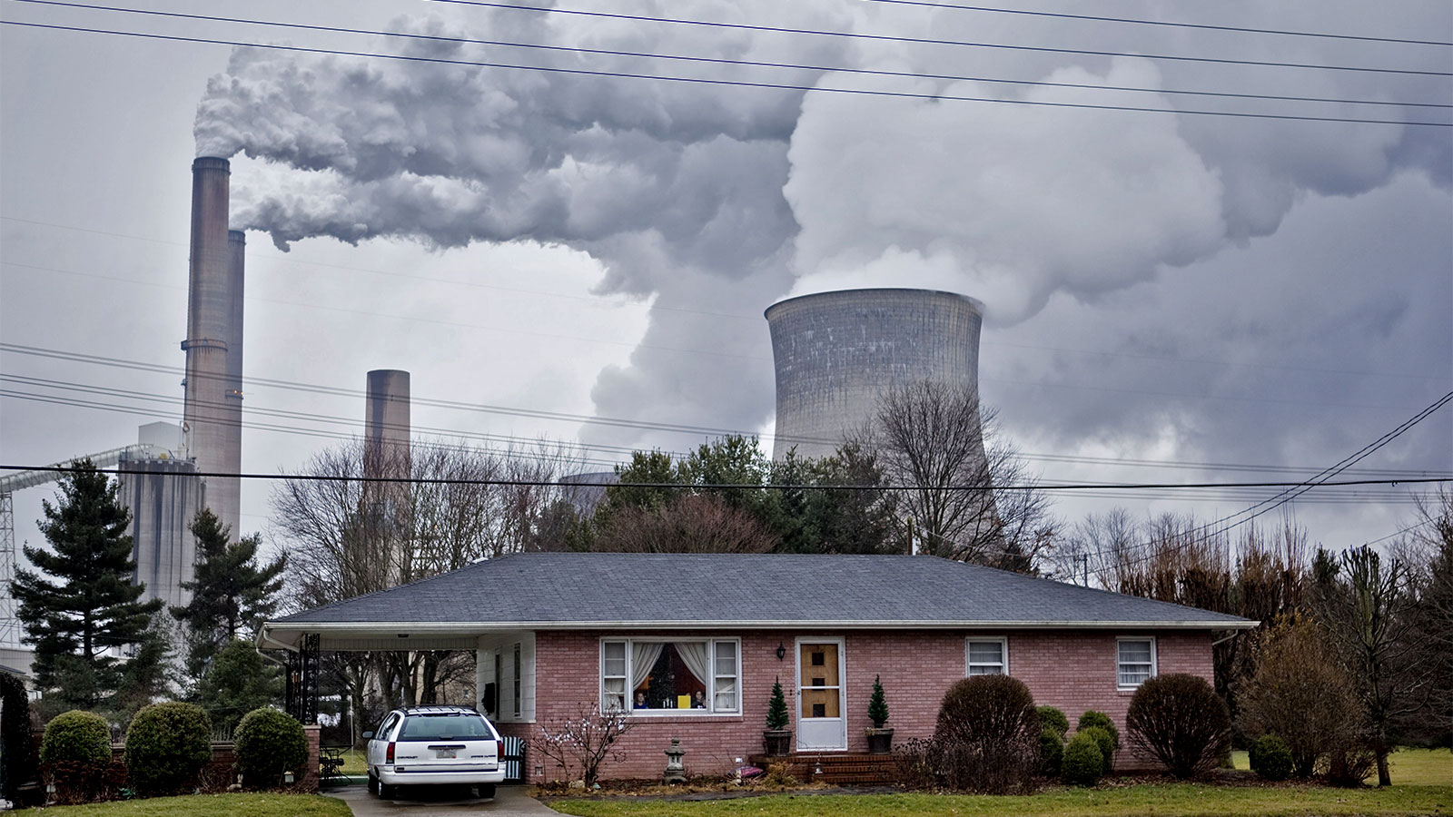 The stacks from the Gavin coal burning power plant dwarf a small nearby home in Cheshire, Ohio