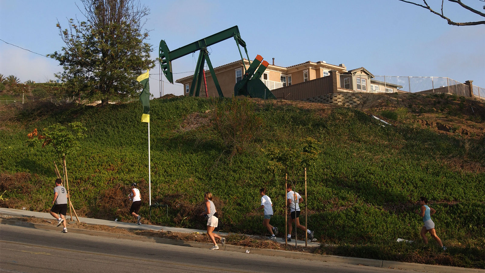 A group of joggers passes an oil well pumping next to residential units under construction in residential California