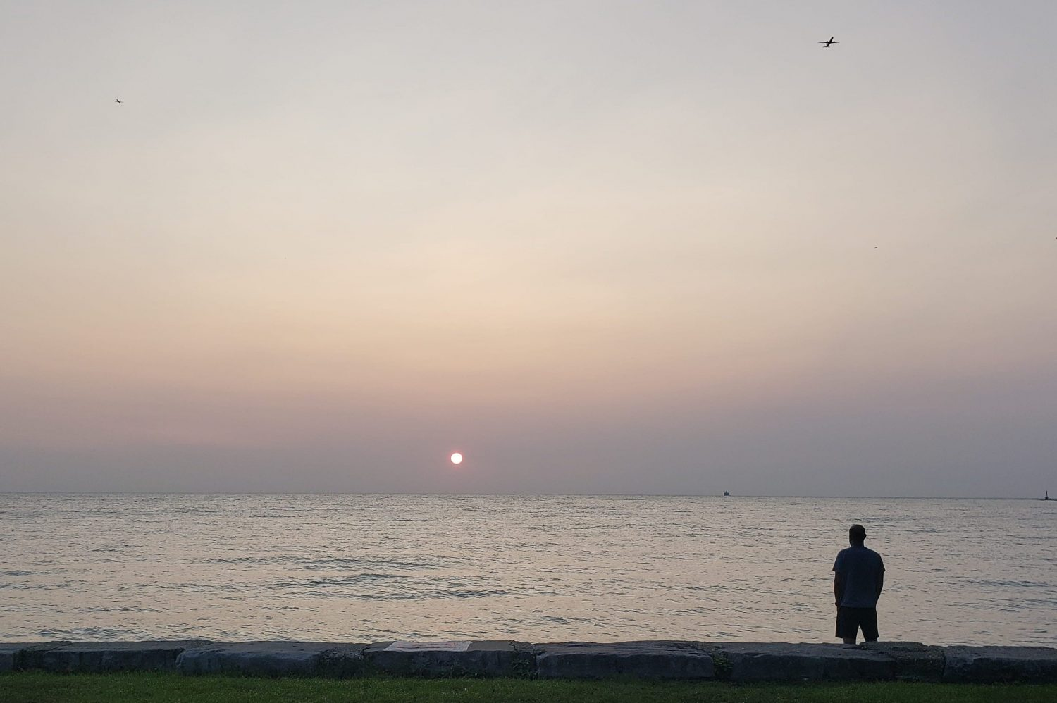 A reddish sun rises in a hazy sky over the lakefront.