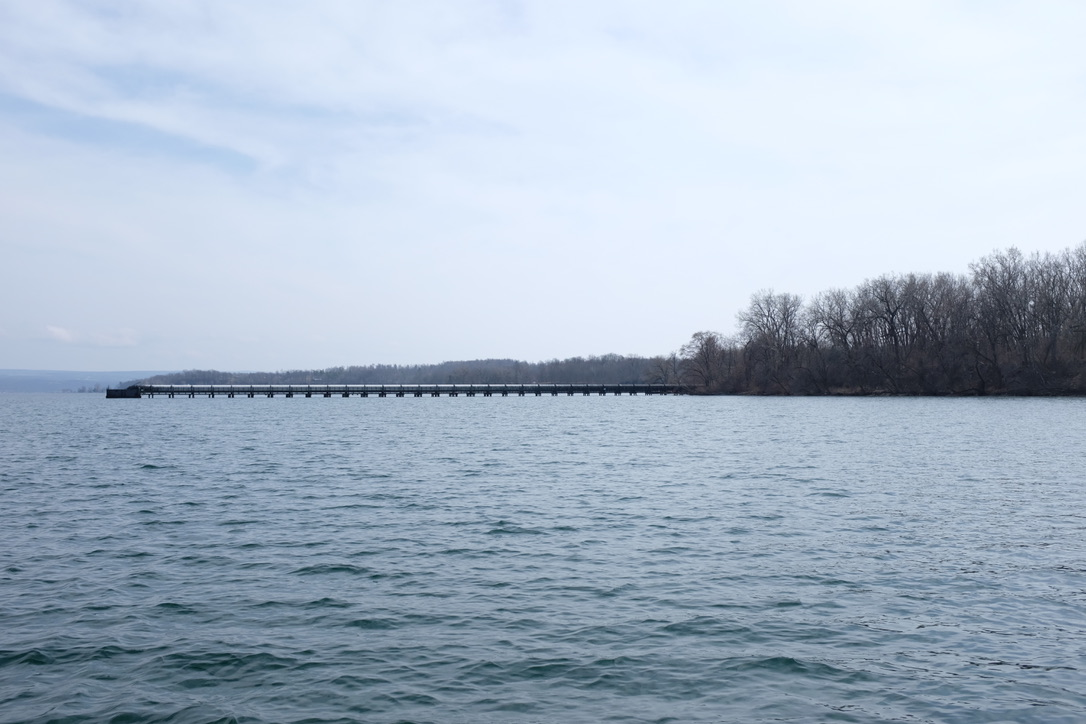 a wide shot of a long metal pipe extending from a woodsy shore into the waters of Seneca Lake