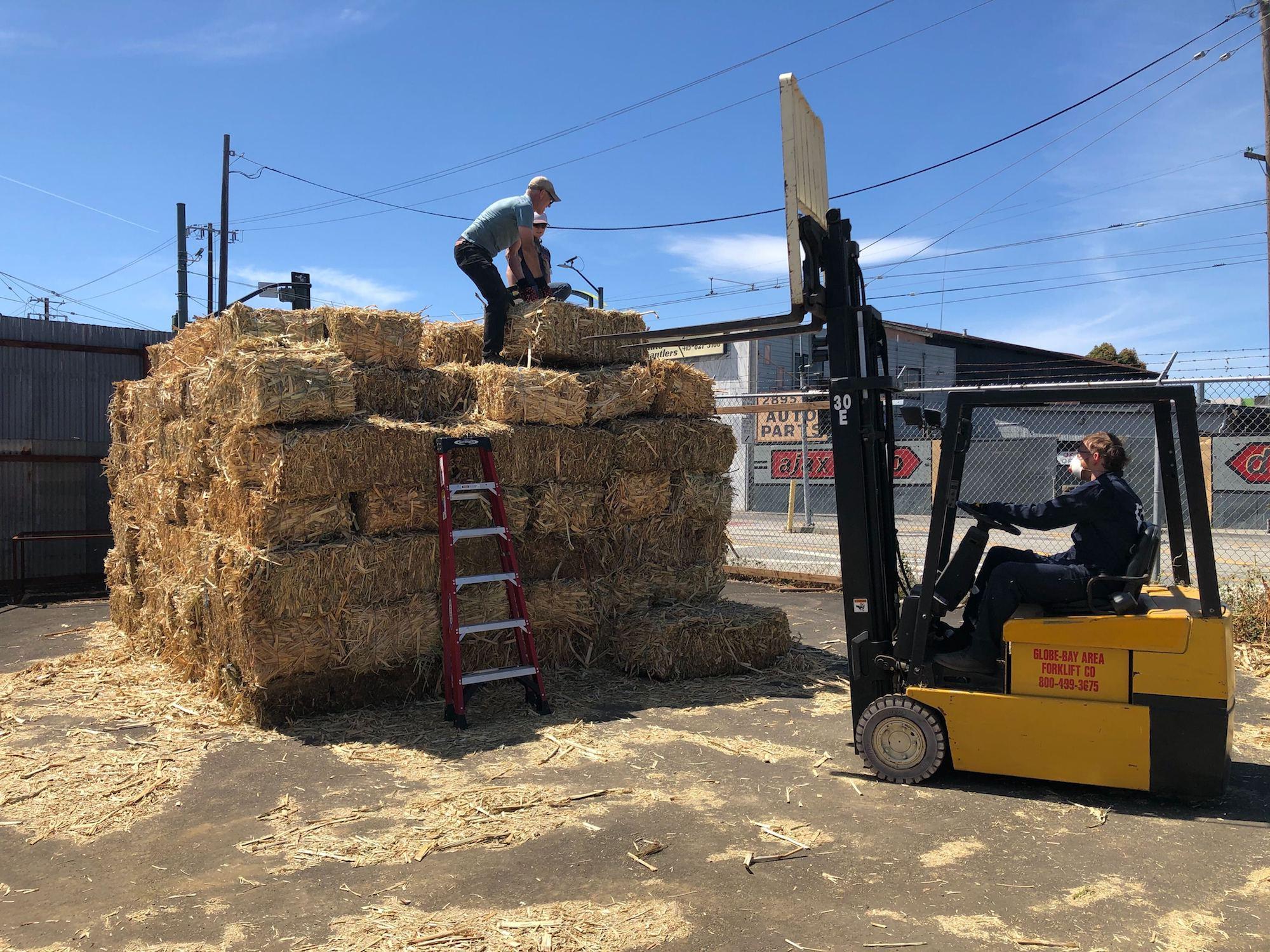 Charm Industrial staffers arrange bales of farm waste.