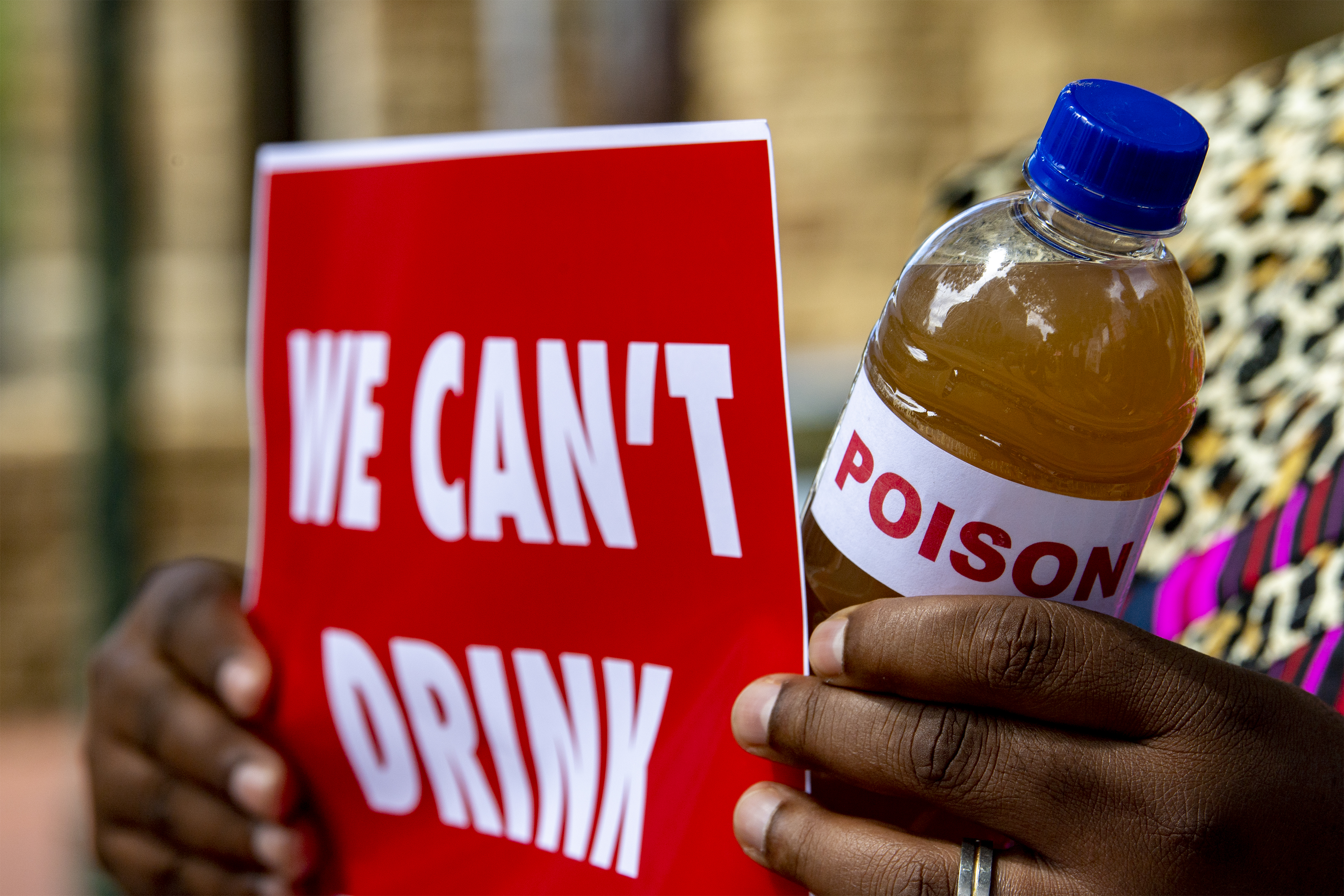 """A picture of a sign that reads """"WE CAN'T DRINK"""" and a bottle of dirty water with a """"poison"""" label on it held by a person at a silent protest against the drilling in the Kavango Basin on the steps of St. George's Cathedral."""