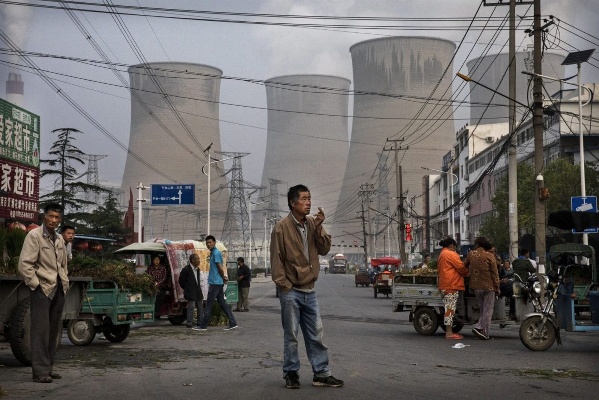 Street vendors and customers are gathered at a local market in front of a coal plant.